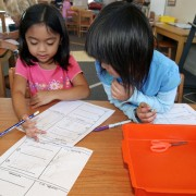 two elementary girls working on math problems in classroom